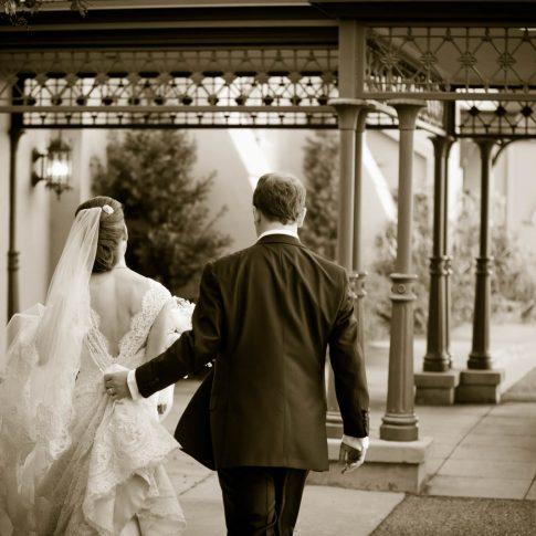 A sepia image of a bride and groom walking to their awaiting chauffeur and Rolls-Royce.