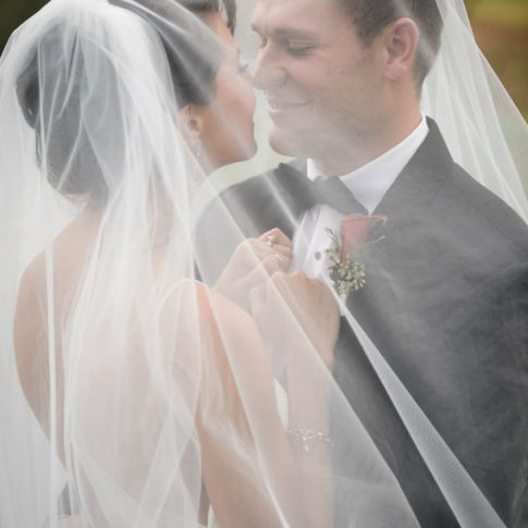 The bride and groom happily smile at each other as they stand draped by the brides veil.