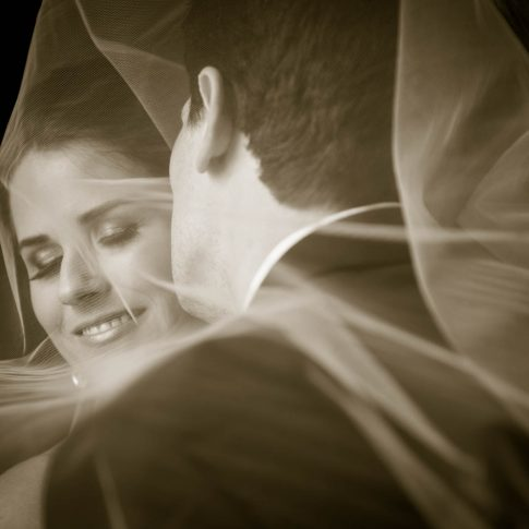 Newlyweds snuggle under veil in sepia photograph