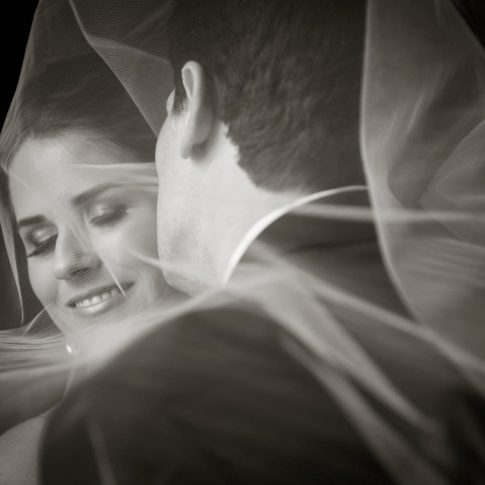 A groom kisses his bride on the cheek as they are both surrounded by her tulle veil.