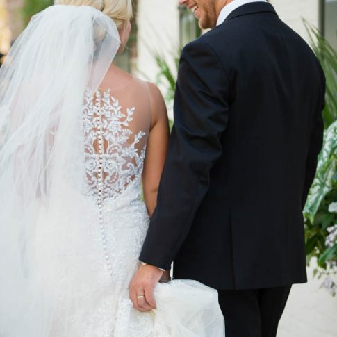 A groom carries his brides train as they walk the streets of downtown Charleston, SC.