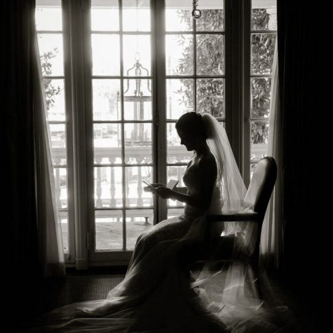 A bride peruses the letter written to her by her groom while getting ready.
