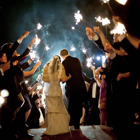 Husband and wife exit the Poinsett Club through a tunnel of sparklers