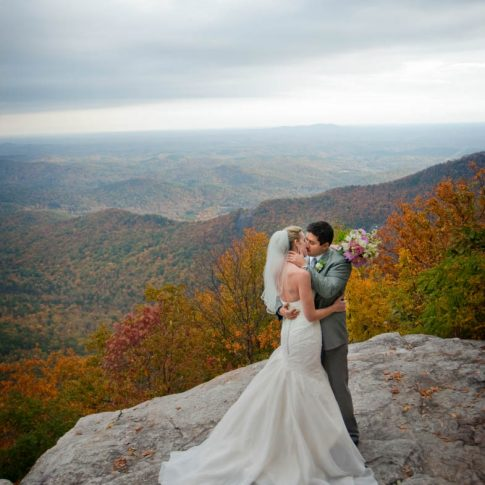 Standing on a boulder overlooking the Blue Ridge mountains outside of Symmes Chapel, newlyweds share a kiss.