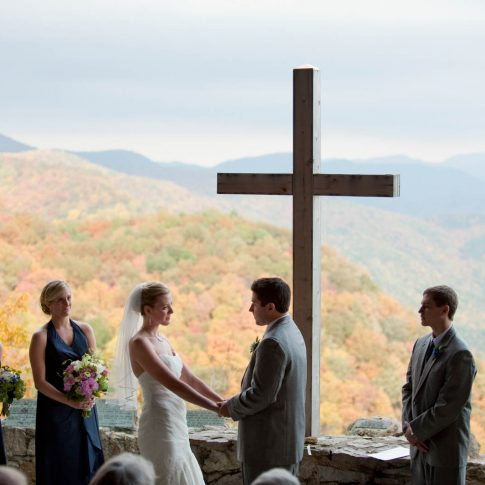 The bride and groom stand, holding hands, at Pretty Place, NC, during their wedding vows.