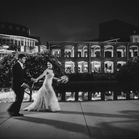 Newlyweds walk hand-in-hand along the sidewalk outside of the Wyche Pavilion as they prepare to join their reception.