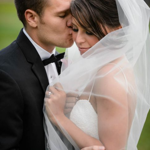 The groom softly kisses his bride on the cheek as she pulls her veil around herself.