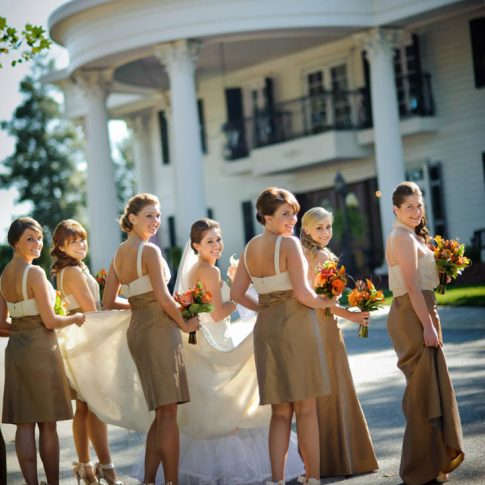 Bridesmaids carefully lift the brides train as they turn back and smile outside of the wedding venue, the Ryan Nicholas Inn.