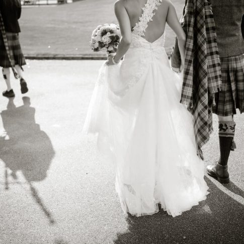 A bride holds her groom's hand as they follow a bagpiper towards their reception venue with their wedding party following closely behind them.