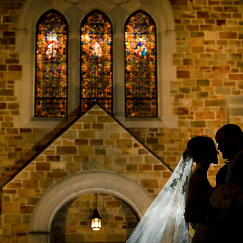 The bride and groom stand outside Spartanburg First Presbyterian Church, where they were married, and are backlit by the lights shining on the church.