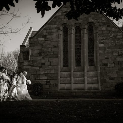The bride and her bridesmaids walk toward the chapel before the ceremony begins.