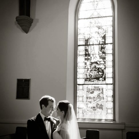 The bride and groom stand in between pews in the St. Johns Episcopal Church where they will be married.