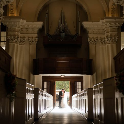 A bride and groom share a kiss while standing in the doorway of the St. Philips church in Charleston, SC.