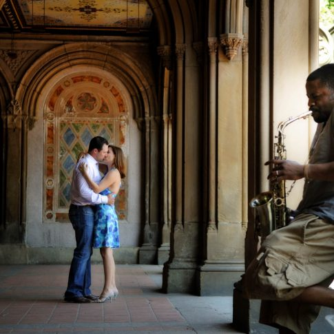 Underneath beautiful historic arches in NYC with a saxophone player in the foreground, an engaged couple shares a romantic kiss.