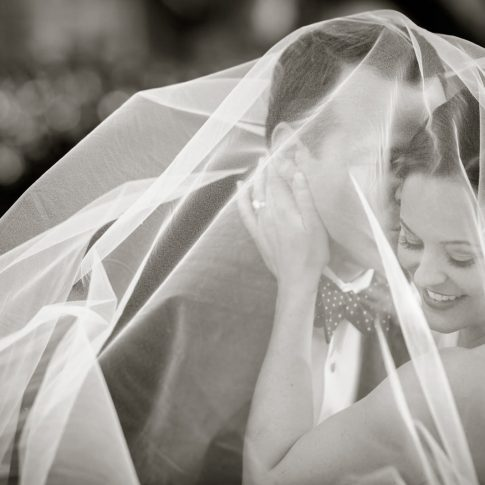 A groom plants a quick kiss on the cheek of his wife as they are both covered in the tulle of her veil.
