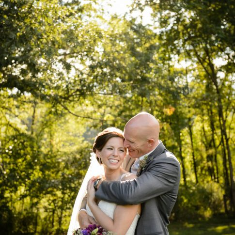 A groom hugs his new wife from behind as they smile and stand surrounded by lush greenery.