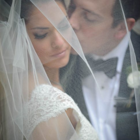 A groom softly kisses her bride underneath her veil.