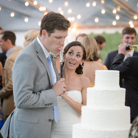 During the cake cutting during the reception, a bride excitedly watches her new husband sample the delicious cake.