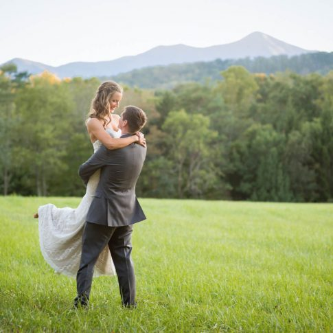 A groom swoops his bride up in his arms as they stand in a lush field in Candler, NC.