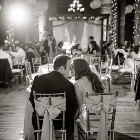 The bride and groom sneak a kiss amongst the business of their wedding reception.