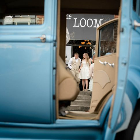 Shot through the door of their getaway car, a couple prepares to exit their reception and say goodbye to their guests.