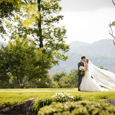 The bride and groom share a kiss surrounded by the green forestry overlooking the mountains in Cashiers, NC.