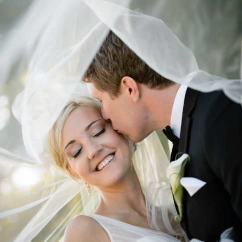 Underneath the swirling of the brides veil the groom plants a loving kiss on the brides cheek.
