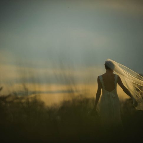 A brides veil blows in the wind as she looks off into the stormy horizon during a bridal portrait session.