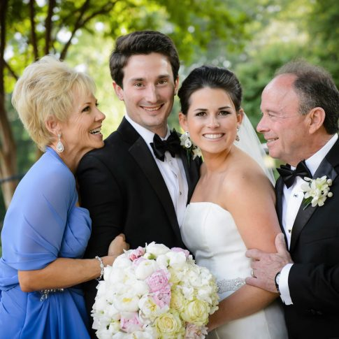 Parents of the bride and groom lovingly embrace the young couple in a moment of excitement and support for the couple.