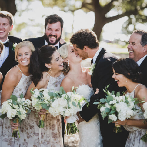 Husband and wife hug and kiss while being surrounded by their wedding party laughing.