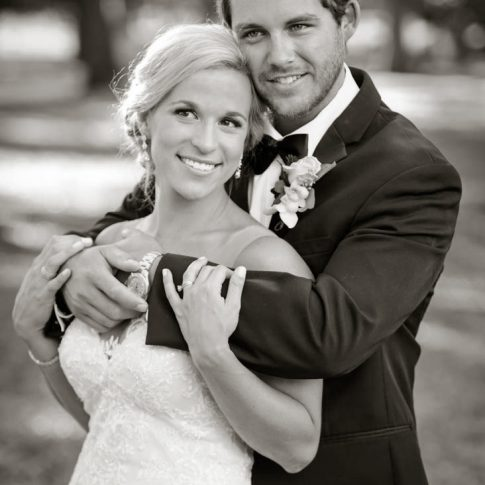 A new husband embraces his wife from behind as they smile happily.