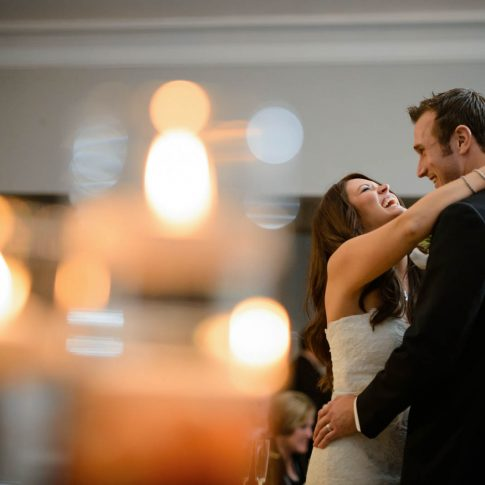 A bride and groom laugh during their first dance.