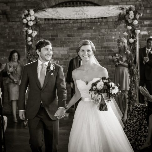 The new husband and wife walk down their aisle during their wedding recessional.