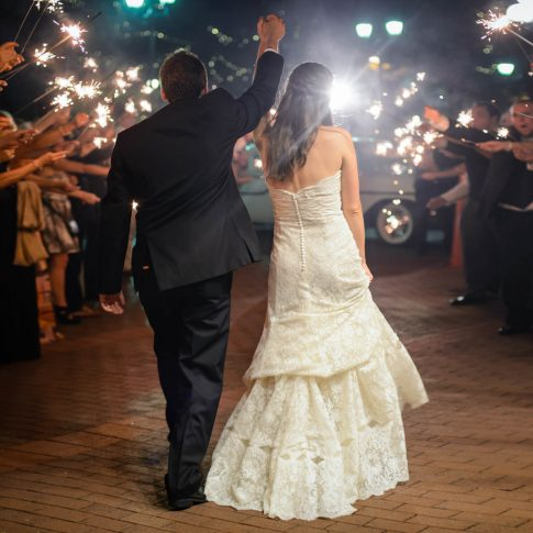 A bride and groom jovially wave goodbye to their guests who wave sparklers in celebration of sending off the happy couple.