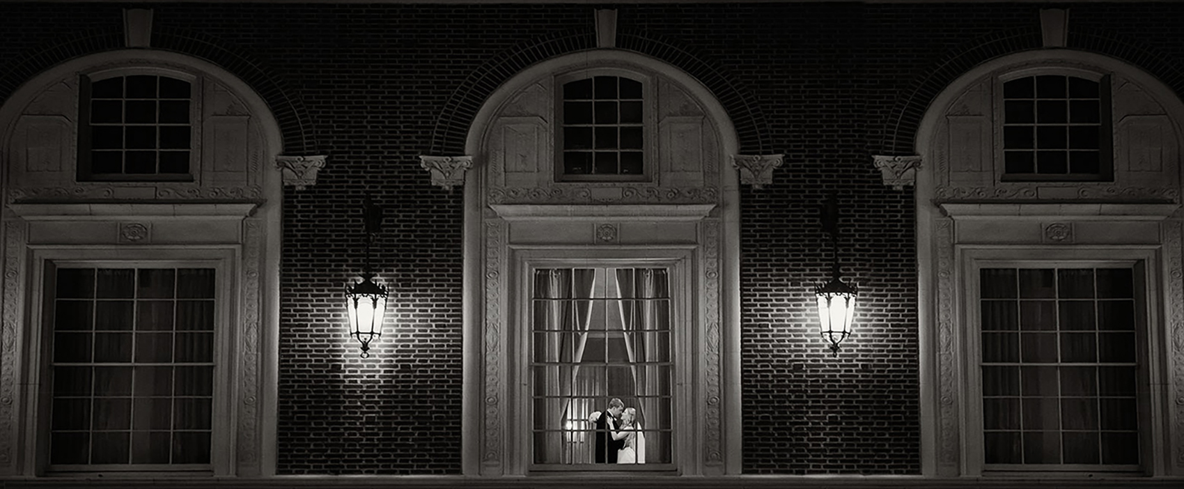 An image captured from outside the Westin Poinsett Hotel in Greenville, SC, peers into the Poinsett Ballroom to see a husband and wife embrace.