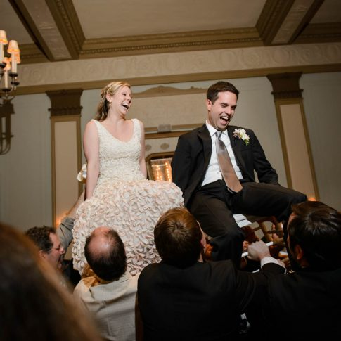 Guests hoist the bride and groom into the air in celebration during their wedding reception.
