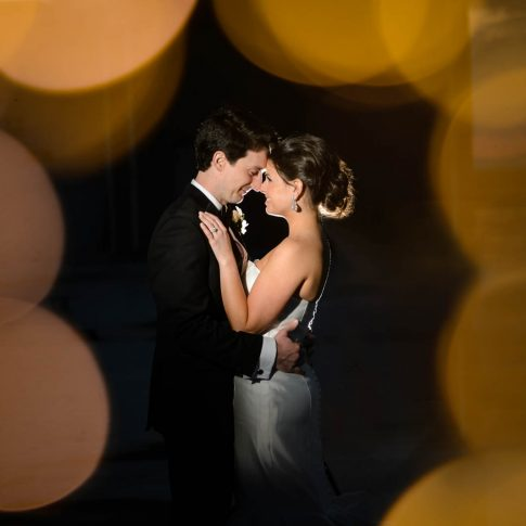 On the rooftop of the Westin Poinsett Hotel, a bride and groom share a happy gaze while the bokeh of the rooftop lights surrounds them.