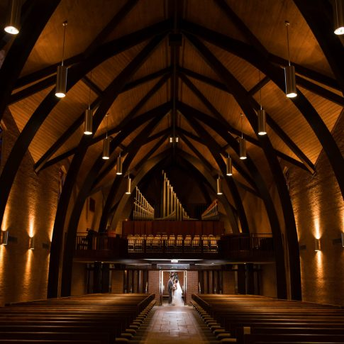 A wide angle photograph of Westminster Presbyterian Church in Greenville, with a bride and groom hugging at the far end of the isle.