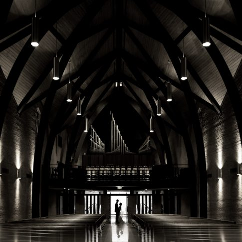 The bride and grooms silhouette appears in the doorway of the dimly lit Westminster Presbyterian Church in Greenville, SC, where they will soon be wed.