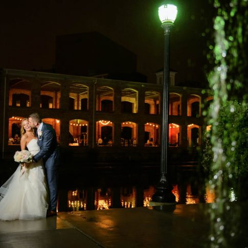 A couple shares a playful kiss outside the Wyche Pavilion while their guests enjoy their reception.