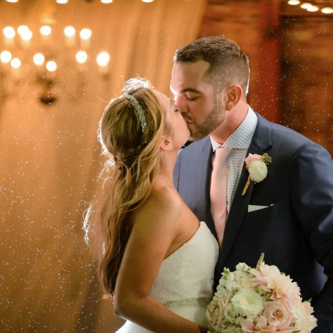 The bride and groom share a kiss as they stand in the beautiful Wyche Pavilion in downtown Greenville, SC.