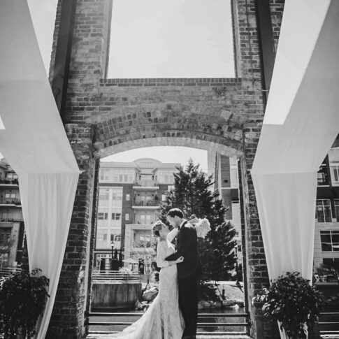 Standing on the ledge of an opening in the Wyche Pavillon in Greenville, SC, the happy bride and groom lovingly gaze at each other.