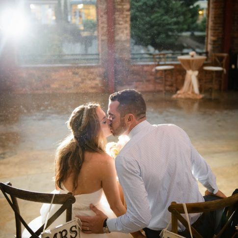 The new Mr. and Mrs. are seated in matching chairs as they share a kiss in the Wyche Pavilion.