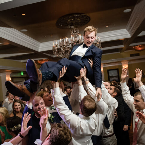 Guests at the reception taking place at the Orangeburg country club lift the groom in excitement and celebration.