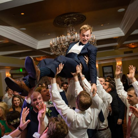 Guests at the a reception taking place at the Orangeburg country club lift the groom in excitement and celebration.