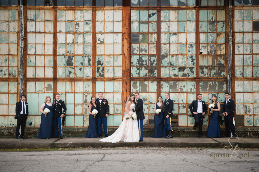 The rustic windows of the mill create a juxtaposition with the wedding party in their fine attire.
