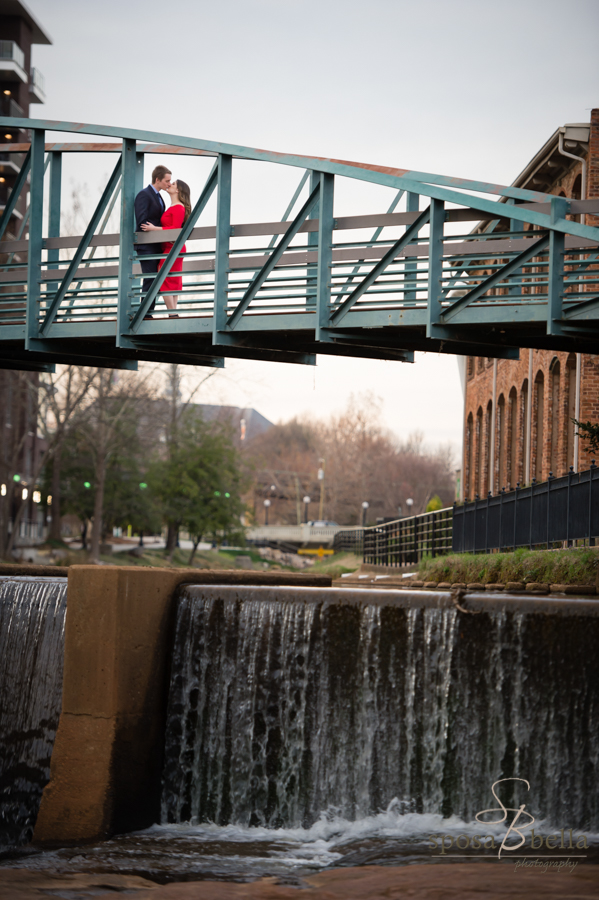The soon-to-be newlyweds share a kiss on the walking bridge across the Reedy River.