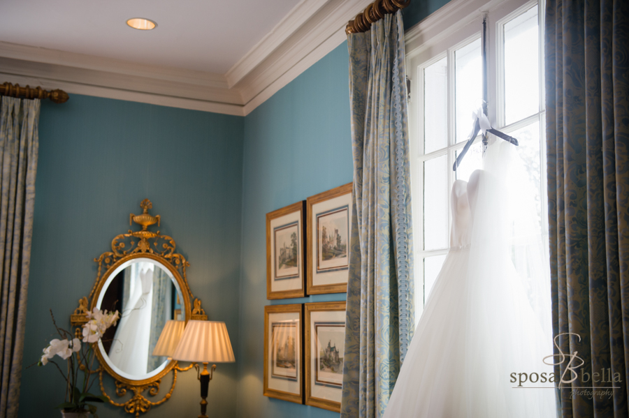 A wedding dress hangs in the window at the Poinsett Club. Notice the reflection on the dress in the mirror. Greenville, SC 2017