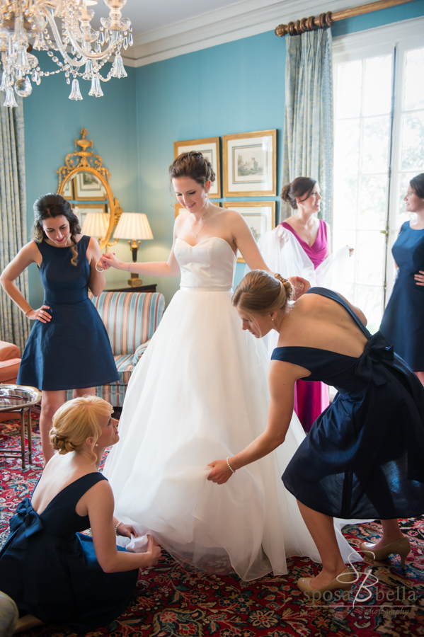 A bride puts on her shoes...with assistance from her bridesmaids in the Friendship room at the Poinsett Club.