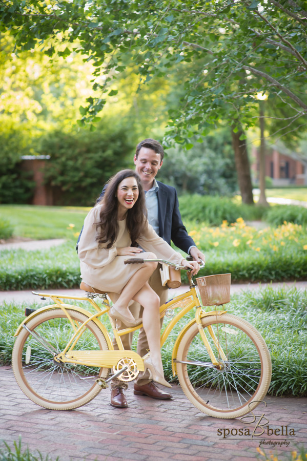 Bride-to-be laughs as her fiance steadies her bicycle.